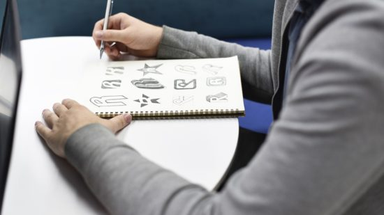 hand-holding-notebook-with-drew-brand-logo-2