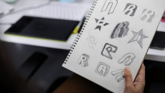 hand-holding-notebook-with-drew-brand-logo