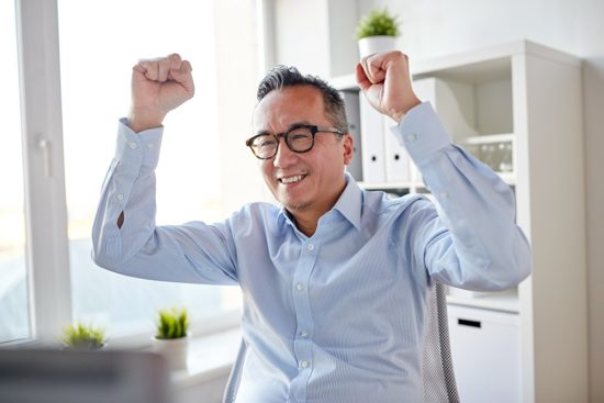 happy-businessman-celebrating-victory-at-office-550x367