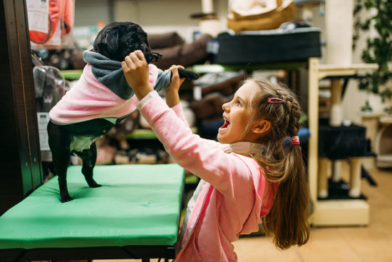little-girl-try-on-clothes-for-puppy-in-pet-shop-550x367