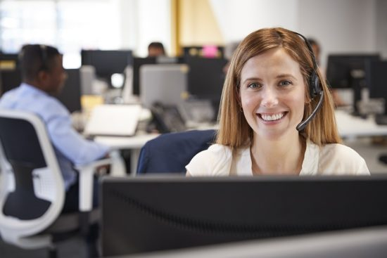 young-woman-working-at-computer-with-headset-in-550x367