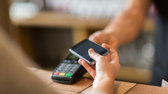 hands-with-payment-terminal-and-smartphone-at-bar