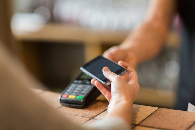 hands-with-payment-terminal-and-smartphone-at-bar-768x512